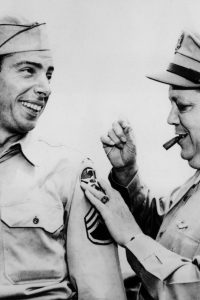 9th June 1944:  Sergeant Joseph P DiMaggio (1914 - 1999), former New York Yankees baseball player, smiles as Brigadier General William J Flood attaches a new 7th AAF shoulder patch to his army uniform and smokes a cigar.  (Photo by APA/Getty Images)